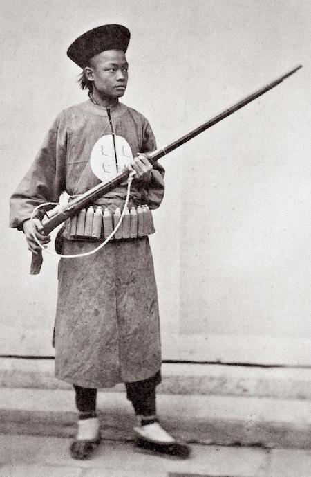 Bild  1874 Manchu-Soldat mit Gewehrwas vermutlich aus der Ming-Zeit stammt